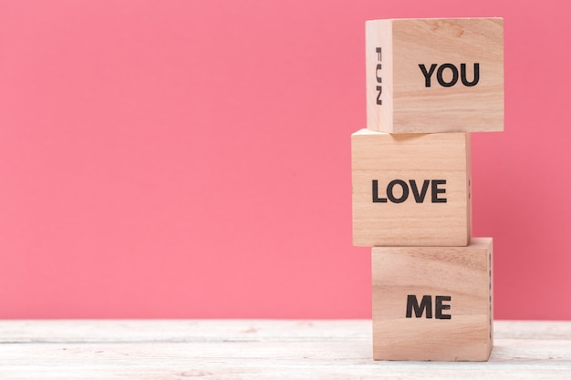 Wooden cubes with text on table over pink  with copyspace for text