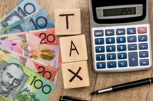 テキスト税オーストラリアドルペンと計算機と木製の立方体