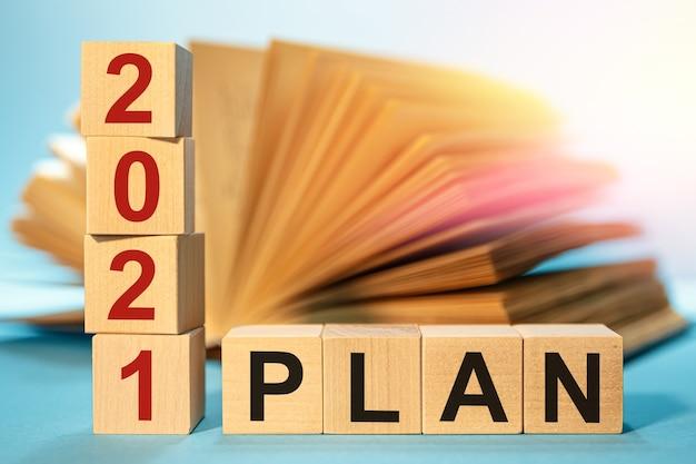 開いた本の背景に略語planと木製の立方体
