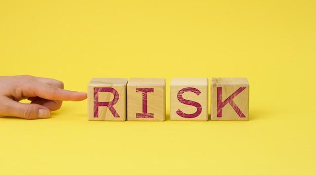 黄色の表面に碑文のリスクがある木製の立方体