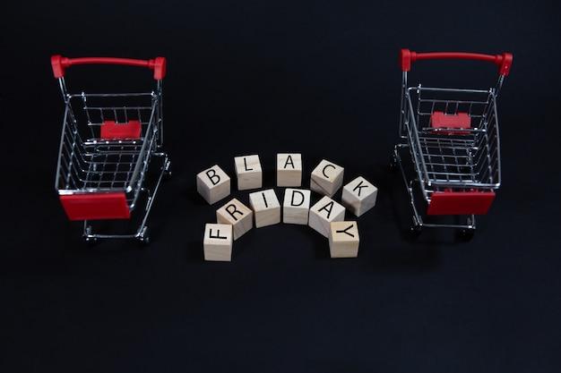Деревянные кубики с надписью черная пятница рядом с тележкой супермаркета