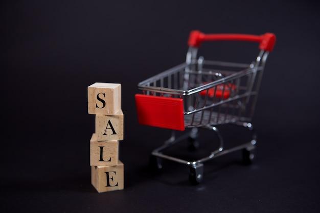 Деревянные кубики с надписью распродажа на черном фоне с корзиной для покупок