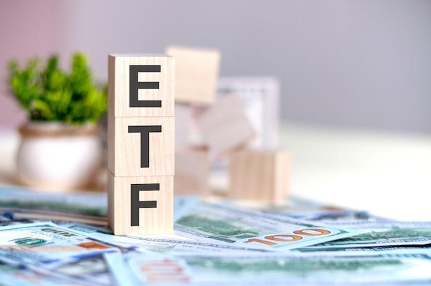 지폐에 수직 피라미드, 배경에 꽃 냄비에 녹색 식물에 배열 된 편지 etf와 나무 큐브. etf-exchange-traded fund의 줄임말, 비즈니스 개념.