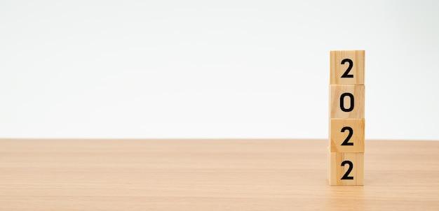 Деревянные кубики с цифрой сверху на деревянном столе с белым фоном