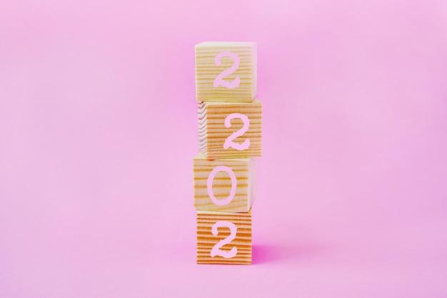 新年の始まり、ピンクの背景にテキスト2022の木製の立方体。