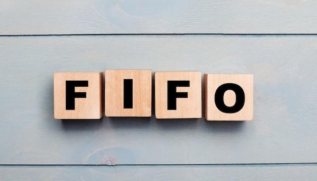 水色の木製の背景にfifo先入れ先出しのテキストが付いた木製の立方体。