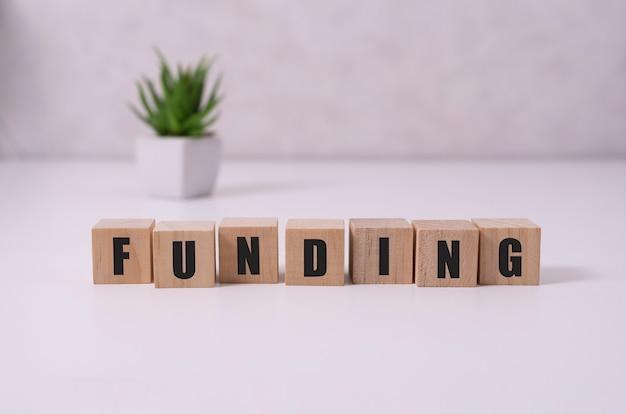 Fundingというテキストが付いた木製の立方体