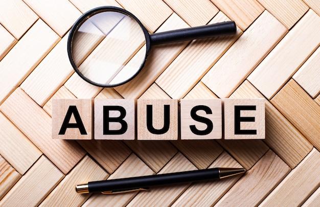 虫眼鏡とペンの間の木製の表面に、「虐待」という言葉が書かれた木製の立方体が立っています。