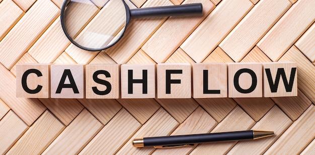 Cashflowという言葉が付いた木製の立方体は、虫眼鏡とペンの間の木製の背景の上に立っています