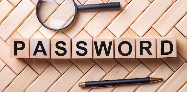 Деревянные кубики с надписью пароль стоят на деревянном фоне между лупой и ручкой.