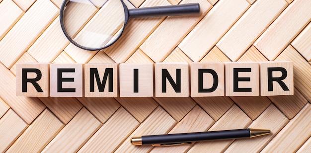 Reminderという言葉が付いた木製の立方体は、虫眼鏡とペンの間の木製の背景の上に立っています
