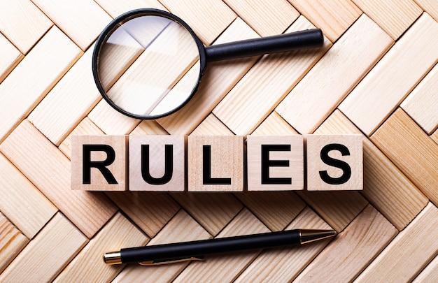 Rules라는 단어가있는 나무 큐브는 돋보기와 펜 사이의 나무 벽에 서 있습니다.