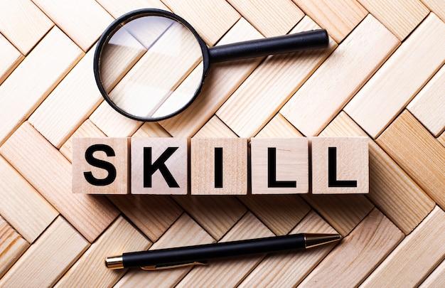 虫眼鏡とハンドルの間の木製の壁に、skillという言葉が書かれた木製の立方体が立っています。