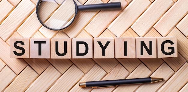 Studyingという言葉が付いた木製の立方体は、虫眼鏡とペンの間の木製の背景の上に立っています