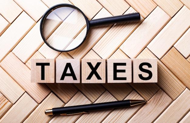 Деревянные кубики со словом налоги стоят на деревянной поверхности между лупой и ручкой.
