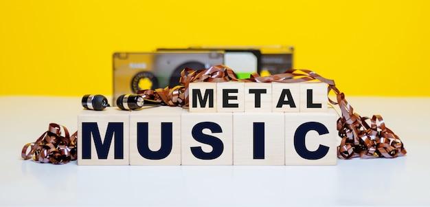 Деревянные кубики с надписью metal music на аудиокассетах и наушниках.