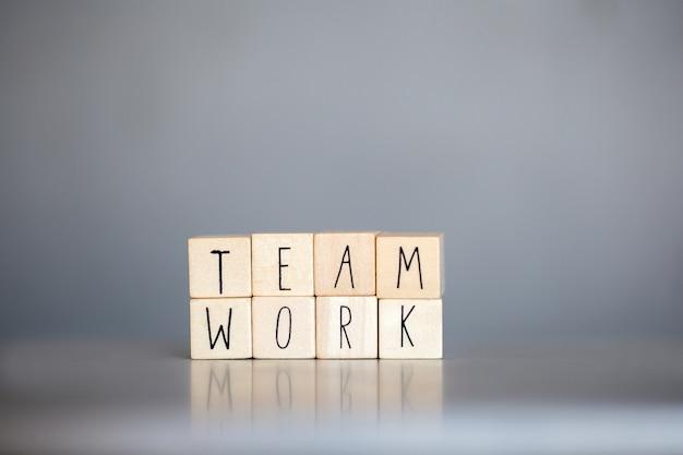 一緒に働く灰色の青い壁にビジネスコンセプトのチームワークという言葉で木製キューブサポート