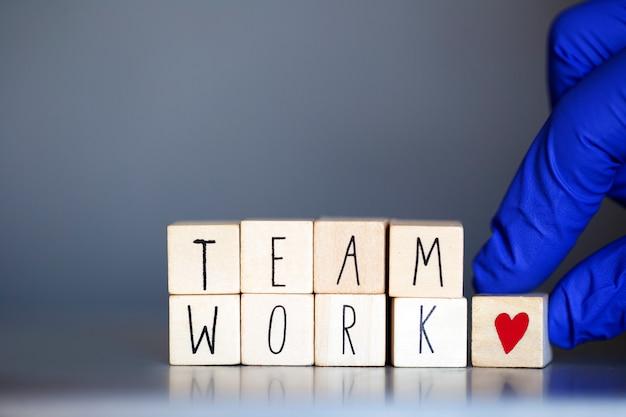 Деревянные кубики со словами team work для бизнес-концепции или медицинских сестер или доктора covid-19, коронавирус, работающие в командах по всему миру