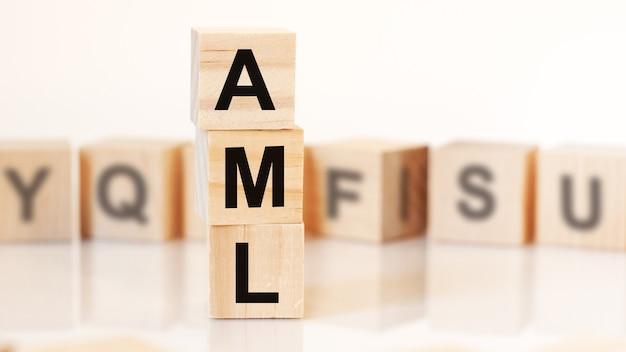 Деревянные кубики со словом aml расположены в вертикальной пирамиде, на белом фоне - ряд деревянных кубиков с буквами, бизнес-концепция. aml - сокращение от anti-money laundering.
