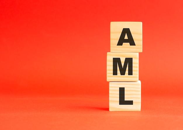 Aml 단어로 나무 큐브입니다. 당신의 디자인과 컨셉을 위해. 빨간색 배경에 나무 큐브입니다. 왼쪽에 여유 공간이 있습니다.