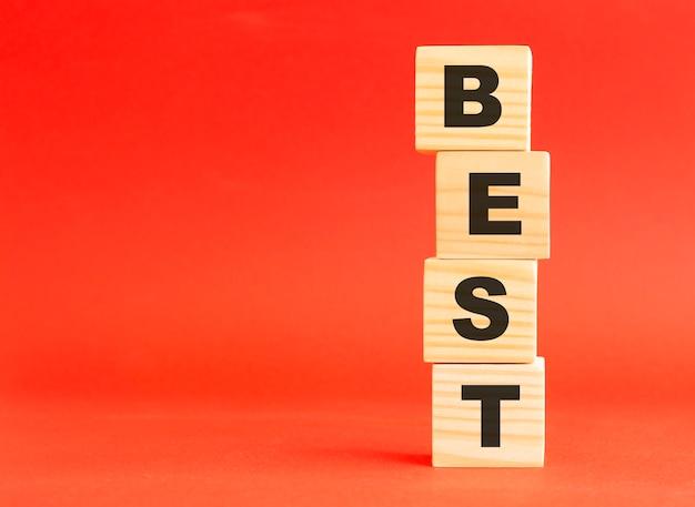 단어 best와 나무 큐브입니다. 당신의 디자인과 컨셉을 위해. 빨간색 배경에 나무 큐브입니다. 왼쪽에 여유 공간이 있습니다.