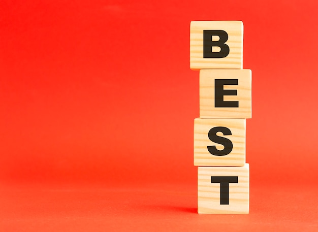 Wooden cubes with word best. for your design and concept. wooden cubes on a red background. free space on the left.