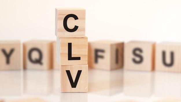 Деревянные кубики со словом clv расположены в вертикальной пирамиде, на белом фоне - ряд деревянных кубиков с буквами, отражение от поверхности стола, бизнес-концепция