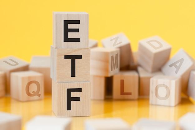 垂直ピラミッドに配置された単語etfの木製の立方体、黄色の表面、文字のある木製の立方体の列、テーブルの表面からの反射