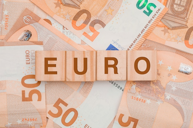 Wooden cubes with word euro on banknote table .