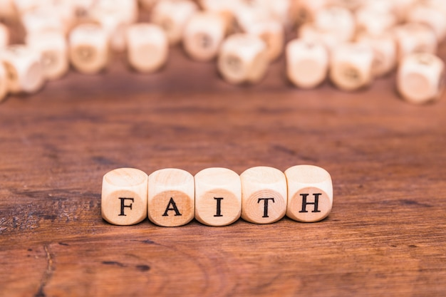 Wooden cubes with word faith on table