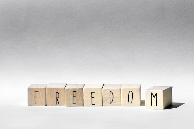 Wooden cubes with the word freedom, freedom concept background close-up