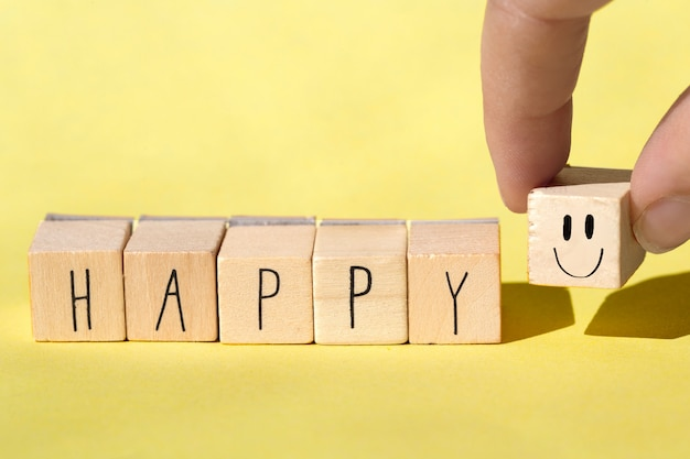 Wooden cubes with the word happy on bright yellow background, cheerful concept