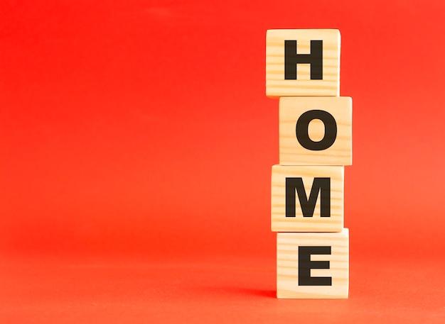 단어 홈 나무 큐브입니다. 당신의 디자인과 컨셉을 위해. 빨간색 배경에 나무 큐브입니다. 왼쪽에 여유 공간이 있습니다.