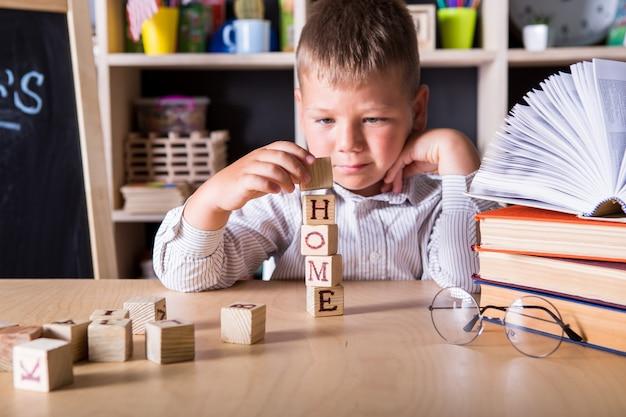 Деревянные кубики со словом домой в руках маленького мальчика дома