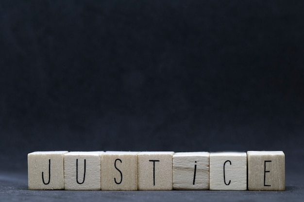 Wooden cubes with the word justice on black background, black lives matter concept