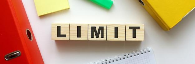 Деревянные кубики со словом limit на офисном столе. папка и другие канцелярские товары.