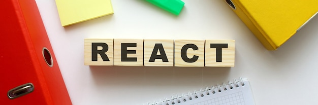 Деревянные кубики со словом react на офисном столе