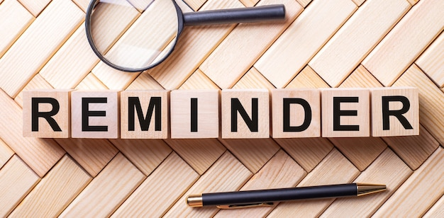 Wooden cubes with the word reminder stand on a wooden background between a magnifying glass and a pen