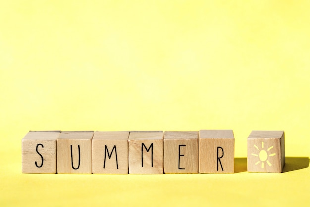 Wooden cubes with the word summer on yellow background, colorful bright summer concept . cheerful