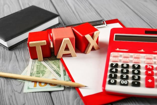 単語taxとテーブルの上の計算機と木製の立方体