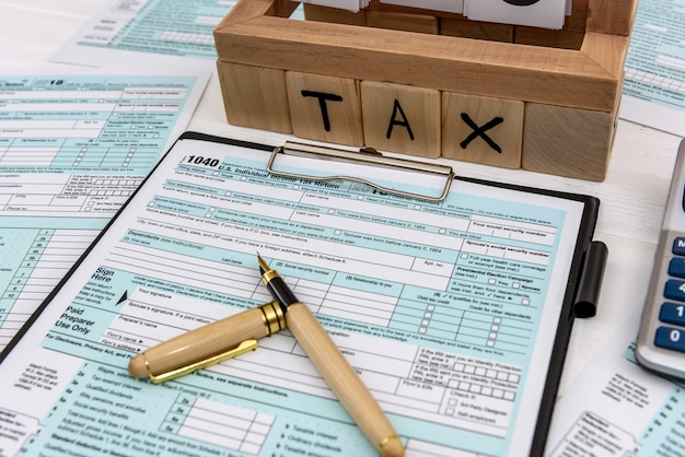 Wooden cubes with word tax and pen on 1040 form