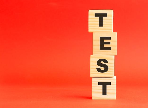 단어 테스트와 나무 큐브입니다. 당신의 디자인과 컨셉을 위해. 빨간색 표면에 나무 큐브입니다. 왼쪽에 여유 공간이 있습니다.