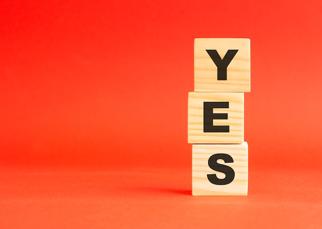 Wooden cubes with word yes. wooden cubes on a red table. free space on the left.