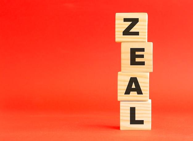 Zeal 단어로 나무 큐브입니다. 당신의 디자인과 컨셉을 위해. 빨간색 배경에 나무 큐브입니다. 왼쪽에 여유 공간이 있습니다.