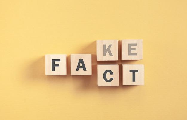 Деревянные кубики со словами fake and fact на желтом фоне.