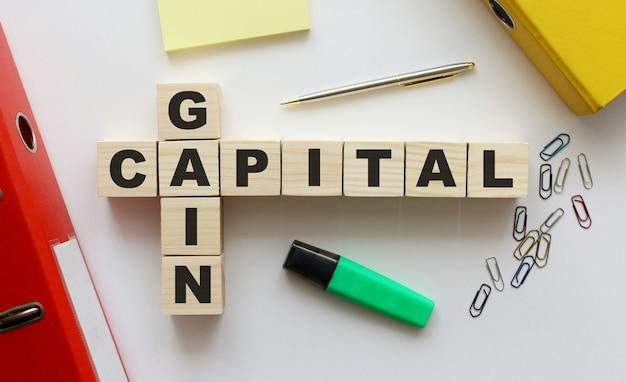 オフィスの机の上にgaincapitalという言葉が書かれた木製の立方体。フォルダーおよびその他の事務用品。