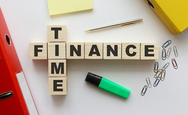 폴더 및 기타 사무 용품이있는 사무실 책상에 단어 time finance가있는 나무 큐브