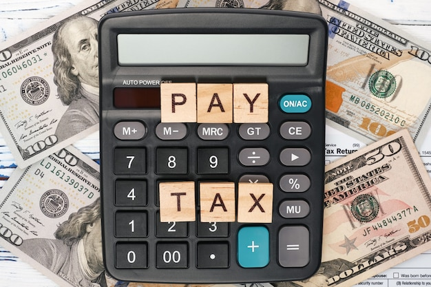 Wooden cubes words pay tax, lying on calculator, tax form 1040 and dollar bills