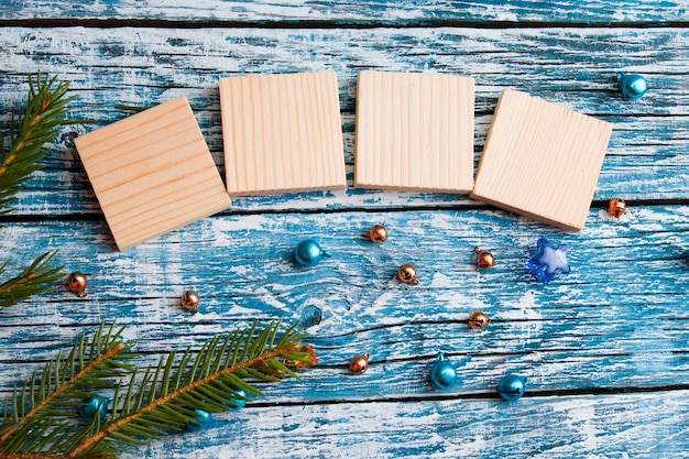 Wooden cubes for your new year dates top view new year concept blue wooden background fir branch