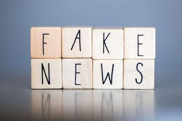 灰色の壁に偽のニュース、偽のニュースのコンセプトのソーシャルメディアの言葉で木製キューブ